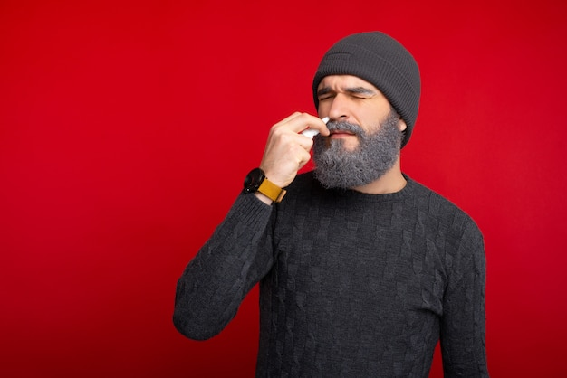 Foto van bebaarde hispter man met een neusspray, neusallergie