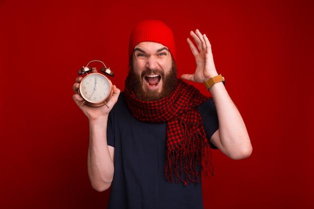 Foto van bebaarde man in rode muts en sjaal, bezorgd en schreeuwen over deadline