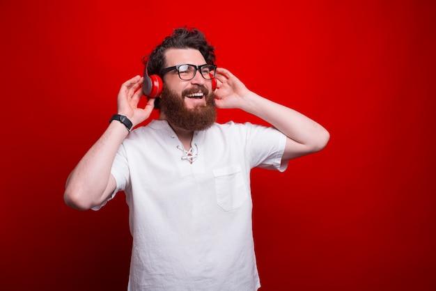 Foto van bebaarde man luisteren muziek op rode achtergrond