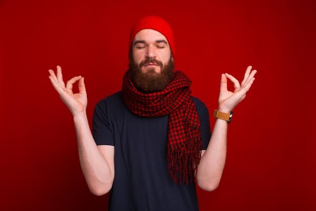 Foto van bebaarde man, met gesloten ogen, zen gebaar, over rode ruimte