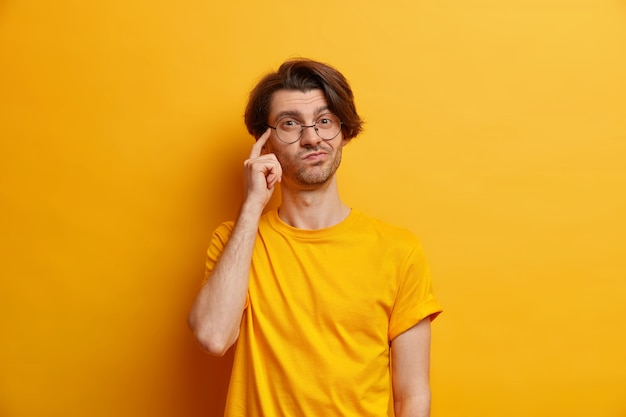 Foto van bedachtzame jonge europeaan houdt vinger op tempel stelt zich voor dat iets een ronde bril draagt en casual t-shirt geïsoleerd over gele muur maakt belangrijke beslissingsvariant