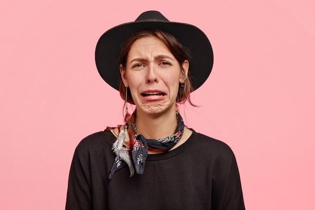 Foto van bedroefde vrouw huilt zoals verdriet heeft, lippen tuit en ontevreden gelaatsuitdrukking heeft, elegante hoed en trui draagt, poseert tegen roze muur