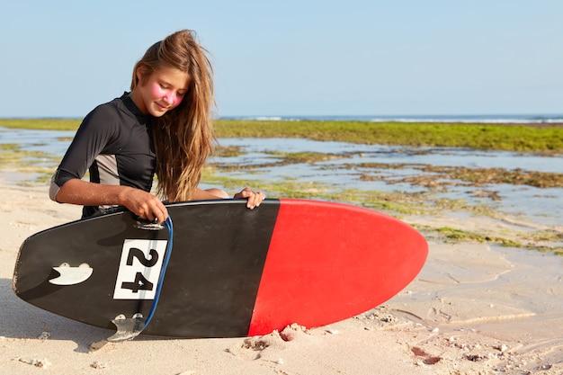 Foto van beginnende vrouwelijke surfer probeert board te repareren, gekleed in een zwart wetsuit, heeft een zink surfmasker op het gezicht