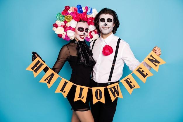 Foto van behoorlijk griezelig paar man dame knuffelen vasthouden gemarkeerd lint aanwezig oktober feestkleding zwarte korte mini-jurk dood kostuum rozen hoofdband bretels geïsoleerde blauwe kleur achtergrond