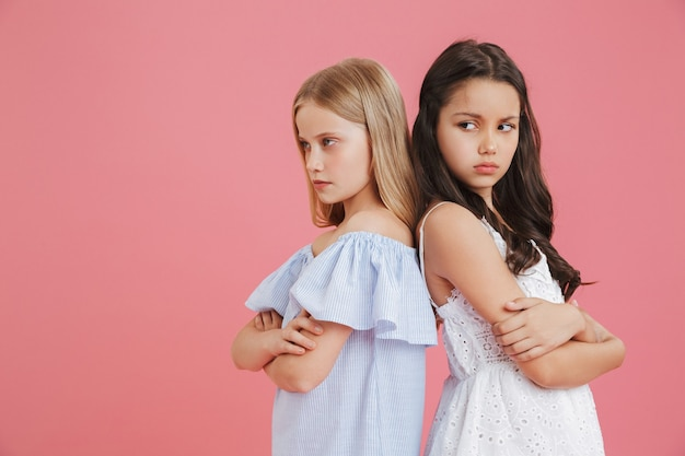 Foto van beledigde brunette en blonde meisjes van 8-10 jaar oud die jurken dragen die rug aan rug staan met gekruiste armen en argument uitdrukken, geïsoleerd op roze achtergrond