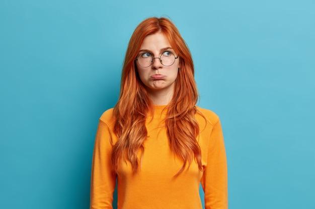 Foto van beledigde roodharige jonge europese vrouw heeft humeurige, teleurgestelde blik, portemonneert lippen en kijkt ontevredenheid weg door onaangename woorden te horen, draagt een casual trui met ronde bril.