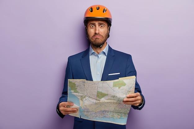 Foto van beschaamd zakenman poseren in stijlvol pak en rode helm op kantoor