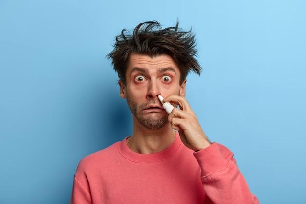 Foto van beschaamde zieke man heeft verstopte neus, gebruikt effectieve medicijnen, houdt een fles neusdruppels vast om vrij te ademen, draagt een roze trui, adverteert met loopneusremedies. mensen, koud, behandeling