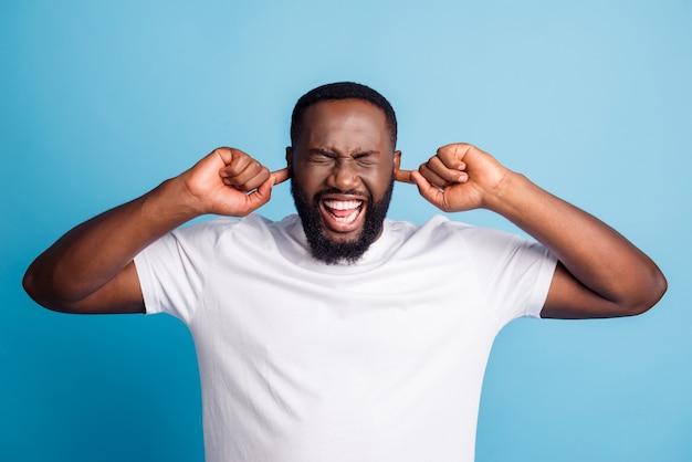 Foto van bezorgde geërgerde man vingers bedekken oren dragen wit t-shirt over blauwe achtergrond
