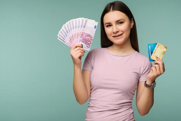 Foto van blanke brunette vrouw glimlachend terwijl creditcard en fan van euro contant over blauw