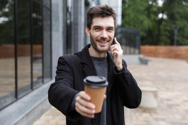 Foto van blanke man 20s met behulp van mobiele telefoon, tijdens het wandelen buiten met afhaalkoffie