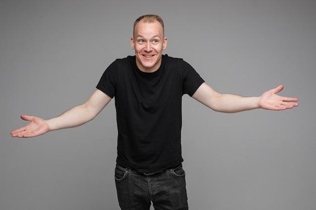 Foto van blanke man houdt zijn handen aan de zijkanten geïsoleerd op een grijze muur