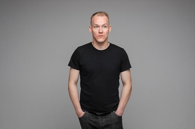Foto van blanke man houdt zijn handen in de zakken van zijn zwarte spijkerbroek geïsoleerd op een grijze muur