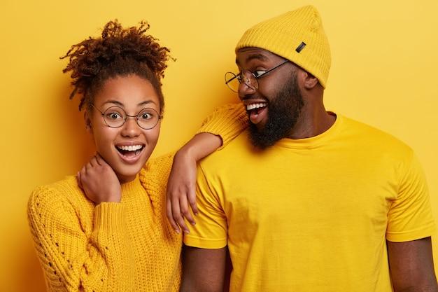 Foto van blij afro-meisje leunt op de schouder van vriendje, voelt zich gelukkig, sta dicht, positieve emoties uiten