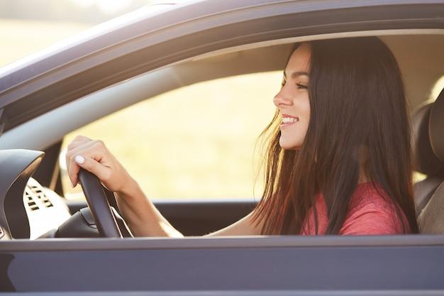 Foto van blij blij brunette vrouwelijke bestuurder kijkt gelukkig naar voorruit