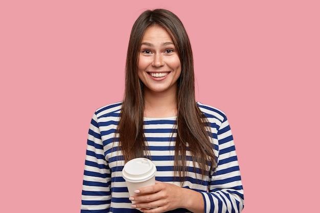 Foto van blij brunette meisje gekleed in casual gestreepte trui, drinkt afhaalkoffie