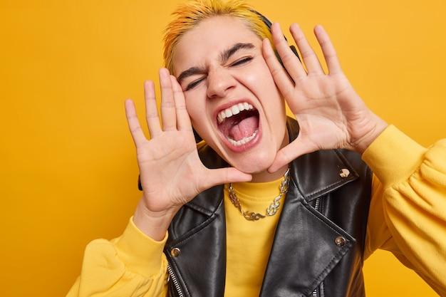 Foto van blij hipstermeisje houdt mond wijd open roept luid handpalmen op schreeuwt toont witte tanden draagt casual trui modieuze leren jas heeft buitengewone uitstraling poseert binnen