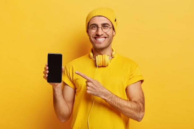 Foto van blij knappe man toont weergave van smartphone, wijst op moderne gadget