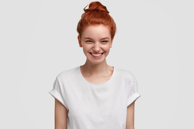 Foto van blij mooie roodharige tienermeisje glimlacht met nieuwsgierige en geïnteresseerde uitdrukking, prachtig aanbod accepteert, draagt casual wit t-shirt, modellen binnen