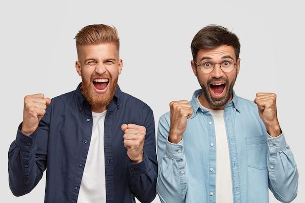 Foto van blije bebaarde mannen die met gebalde vuisten gebalde vuisten heffen, optimisme voelen