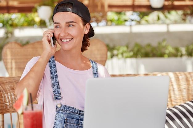 Foto van blije blauwogige vrouw in modieuze pet, spreekt met vriend op slimme telefoon, kijkt gelukkig weg, downloadt nieuwsapplicatie op draagbare laptopcomputer, drinkt verse cocktail in café