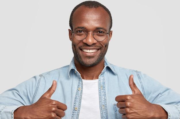 Foto van blije donkere huid volwassen man met stoppels werpt duimen op en glimlacht breed