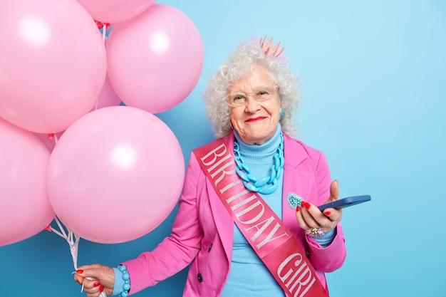 Foto van blije gerimpelde vrouw geniet van verjaardagsviering gebruikt moderne mobiele telefoon krijgt felicitatiesberichten ziet er mooi uit voor haar ouderdom houdt opgeblazen ballonnen draagt feestelijke kleding