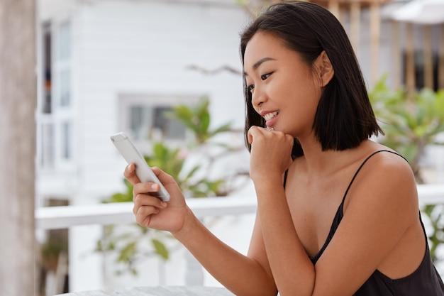 Foto van blije japanse vrouw kijkt grappige video op sociale netwerken via mobiele telefoon, zit op terrasje, geniet van chatten met vriendje, sms-berichten, gebruikt gratis wifi, werkt informatie bij.