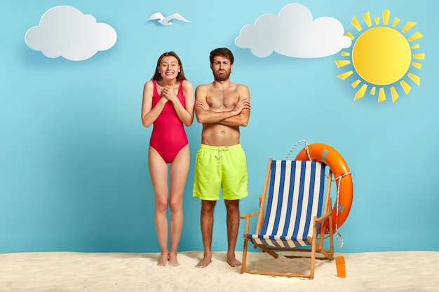 Foto van blije jonge europese vrouw houdt de handen bij elkaar, heeft een slank figuur, gekleed in een rode bikini