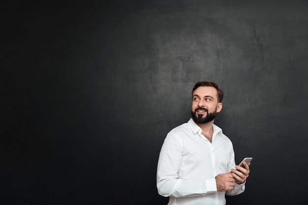 Foto van blije man in wit overhemd terugkijkend tijdens het chatten of het gebruik van draadloze internetin op mobiele telefoon over donkergrijs