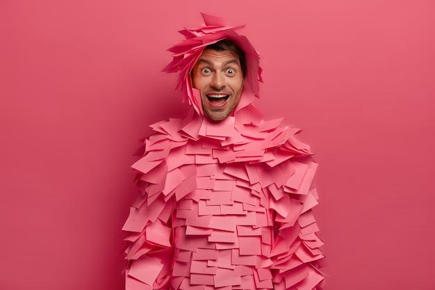 Foto van blije positieve vrouw kijkt met verwondering en geluk, heeft speelse bui, giechelt om grappige grap, maakt papieren outfit van stickers, geïsoleerd op roze muur, heeft hilarisch gepraat