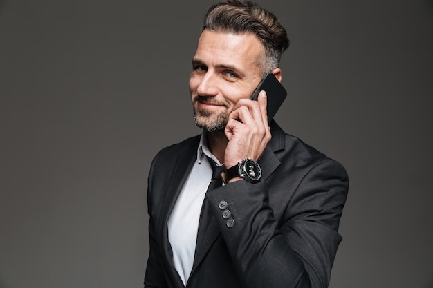 Foto van blije volwassen man in zwart pak praten over smartphone dragen horloge op pols, geïsoleerd over donkergrijs