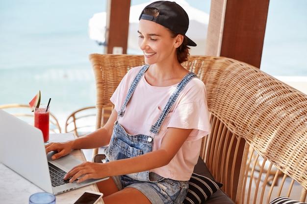Foto van blije vrouw in stijlvolle kleding toetsenborden op laptopcomputer noodzakelijke informatie, surfer internet, omringd met moderne technologieën, drankjes cocktail of smoothie in gezellige cafetaria