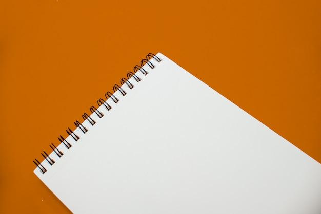 Foto van blocnote op oranje achtergrond met exemplaarruimte.