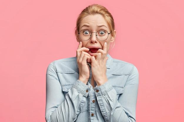 Foto van blonde blauwogige vrouw met nerveuze blik, houdt vingers in de mond, staart naar de camera, voelt zich bezorgd als afraids naar de tandarts gaat, draagt modieuze spijkerjasje,