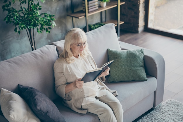 Foto van blonde schattige oude oma zitten comfortabele sofa divan lezen favoriete historische roman boek mooie vrije tijd beige pastel kleding platte woonkamer binnenshuis dragen