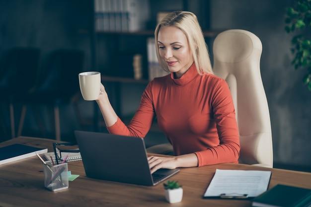 Foto van blonde, vrolijke, positieve programmeur die aan haar nieuwe software voor het bedrijf werkt.ze werkt voor het houden van mok op het bureaublad