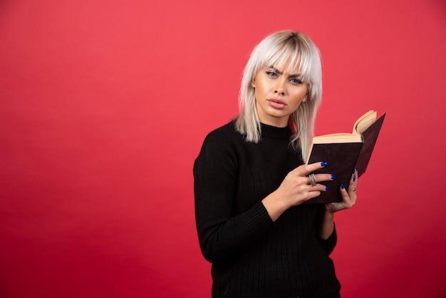 Foto van blonde vrouw die een boek vasthoudt en naar de camera kijkt