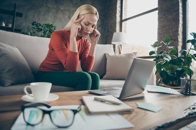 Foto van blonde zakelijke dame moe hardwerkende tempels lijden vreselijke migraine slijtage specificaties oranje pullover zittend bank tafel notebook dagboek koffie binnenshuis