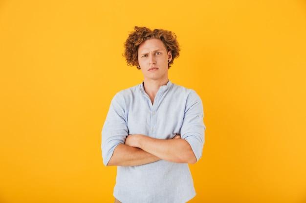 Foto van boos ernstige man met krullend haar staan met gevouwen armen, geïsoleerd op gele achtergrond