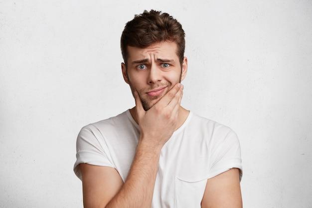 Foto van boos man met stoppels, gekleed in wit t-shirt, krommen gezicht, geïsoleerd op witte achtergrond. ontevreden jongeman draagt casual kleding, heeft een hekel aan iets. mensen en emoties concept