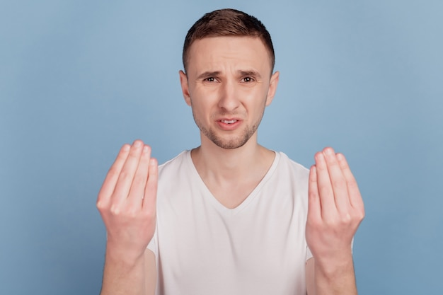 Foto van boos ontevreden jonge bruinharige man probleem geïrriteerd geïsoleerd op blauwe kleur achtergrond