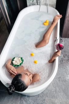 Foto van boven: meisje poseert liggend in een schuimbad, met een bloem en eenden, met een glas rode wijn in haar hand, genietend van ontspanning. genot. persoonlijke verzorging.