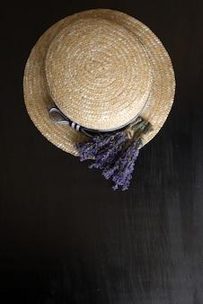 Foto van bovenaf op zwart hout is een bruine hoed met gedroogde bloemen van provençaalse kruiden. bovenaanzicht