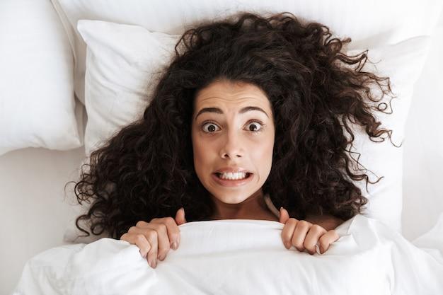 Foto van bovenaf van grappige gespannen vrouw 20s met donker krullend haar grimassen, liggend in bed onder een witte deken