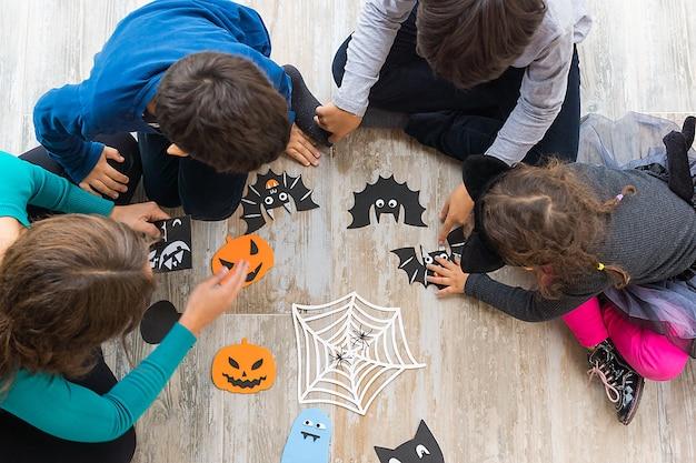 Foto van bovenaf van twee jongens en een meisje met hun moeder zittend op de vloer en bezig met het maken van ambachten voor halloweenversiering