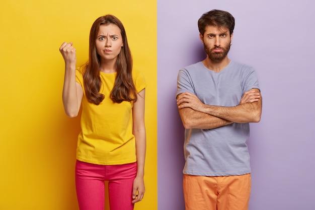 Foto van boze geïrriteerde vrouw heft gebalde vuist, drukt negatieve emoties uit, draagt gele casual t-shirt en roze broek, trieste man houdt armen gevouwen, voelt zich beledigd, misbruikt door iemand