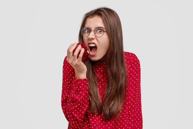 Foto van boze, hongerige jonge vrouw bijt appel met ergernis, in een slecht humeur als dieet houdt, wil eten