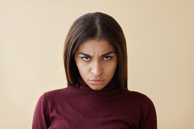 Foto van boze jonge donkerbruine vrouw met een sinistere uitstraling, starend van onder haar gefronste wenkbrauwen, woedend lippen grijpend, haar blik vol woede en irritatie