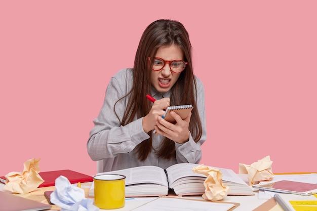 Foto van boze verontwaardigde jonge vrouwelijke auteur legt informatie vast met geïrriteerde uitdrukking, klemt tanden van woede, houdt pen en spiraalvormig notitieboekje vast